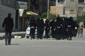 """Female school students wearing a full veil (niqab) walk along a street in the northern province of Raqqa March 31, 2014. The Islamic State in Iraq and the Levant (ISIL) has imposed sweeping restrictions on personal freedoms in the northern province of Raqqa. Among the restrictions, Women must wear the niqab, or full face veil, in public or face unspecified punishments """"in accordance with sharia"""", or Islamic law. REUTERS/Stringer   (SYRIA - Tags: POLITICS CIVIL UNREST CONFLICT RELIGION SOCIETY EDUCATION TPX IMAGES OF THE DAY) - RTR3JCN7"""